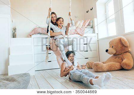 Group of children laughing and playing together, three girls having fun and swinging in bright scandinavian playroom. Kids paljamas party in white bedroom interior.