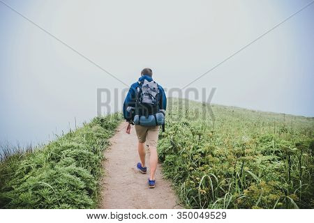 Male Tourist With A Large Backpack Walks His Back Through The Wild In The Fog