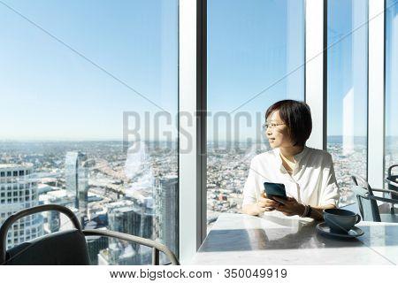 asian female using smart phone in offic restaurant beside window