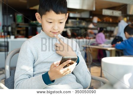 asian boy using smart phone while have breakfast