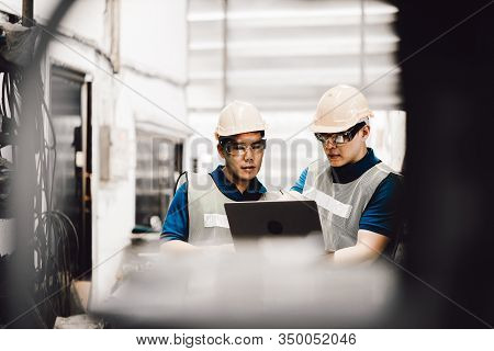 Mechanic And Staff Engineer Talking Nearby A Machine In A Big Factory About Latest New Planing, Two