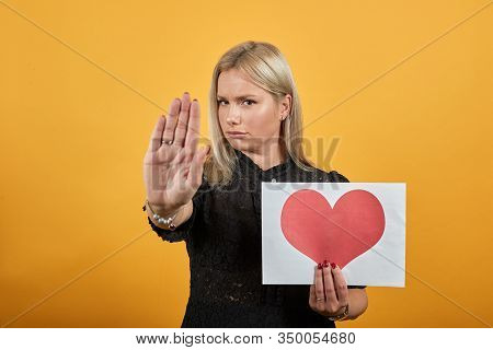 Beautiful Blonde Girl In Black Dress On Yellow Background Upset Unhappy Woman Holding Piece Of Paper
