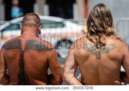 New York, Usa - June 22, 2019: On A Hot Summer Day, Two Sunburned Men With Tattoos On Their Backs Ar