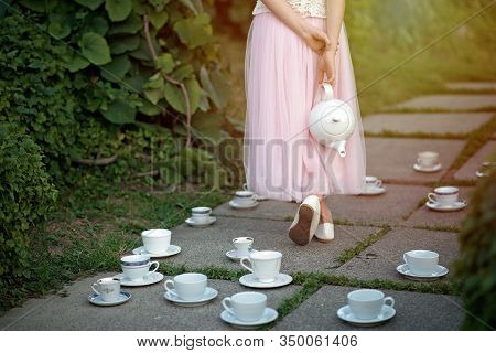 Alice In Wonderland. A Girl In A Full Skirt With A Teapot In Her Hands Among A Set Of Cups And Sauce