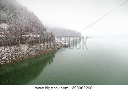 Winter Snowy Day In Bicaz Lake Side At Mount Izvorul Dam, Located In Piatra Neant, Romania