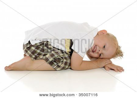 An adorable young preschooler on the floor scrunching up.  On a white background.