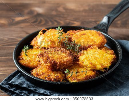 Potatoes Pancakes Latkes, Flapjacks, Hash Brown Or Potato Vada On Brown Wooden Table. Copy Space For