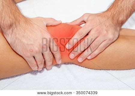 chiropractor or physiotherapist doing a massage to an injured sports person