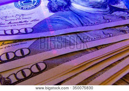 Extreme Closeup On Dollar Banknote Under Ultraviolet Light. Benjamin Franklin Portrait Being Inspect