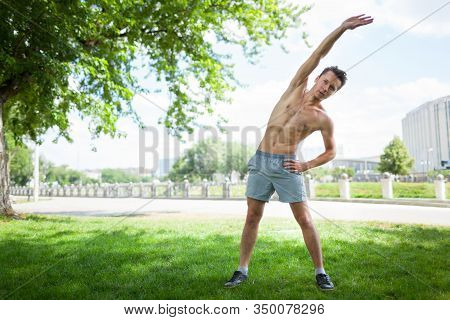 Front View Of Handsome Gentleman With Naked Torso Doing Morning Gymnastics Outdoors. Sporty Young Ma