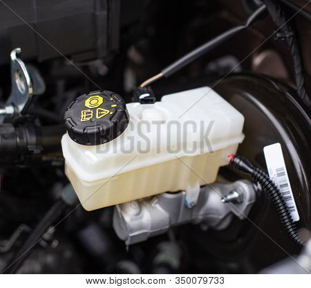 The Tank With Brake Fluid In The Car In The Engine Compartment. The Concept Of The Working Brake Sys