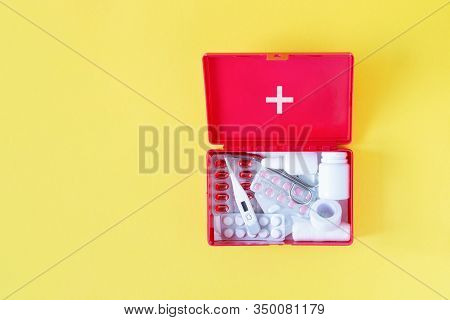 First Aid Kit Red Box With Medical Equipment And Medications For Emergency Top View On Pastel Yellow