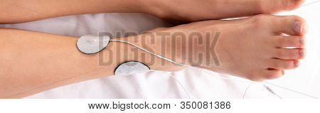 Top View Of Woman Lying On Massage Couch During Electrotherapy Of Leg, Panoramic Shot