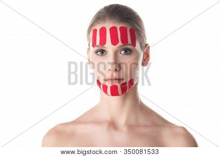 Attractive Young Woman With Kinesiology Tapes On Forehead And Chin Looking At Camera Isolated On Whi