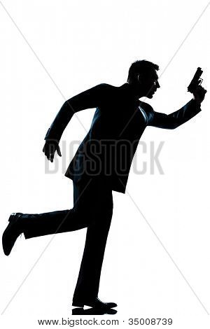 spy criminal policeman detective  man running holding gun full length silhouette in studio isolated white background