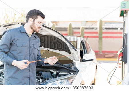 Confident Male Worker Checking Engine Oil With Dipstick At Gas Station