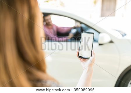 Cropped Hand Of Mid Adult Woman Using Smartphone With Blank Screen Against Car