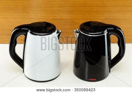Painted Stainless Steel Cordless Electrical Kettle With Black Plastic Handle On The Marble And Woody