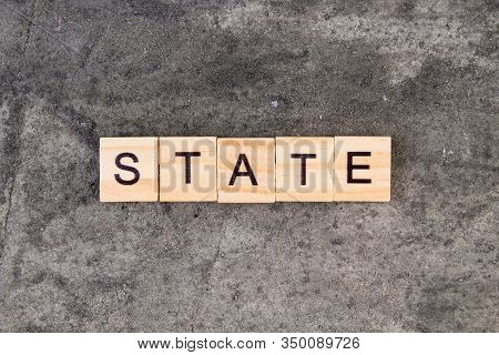 States Word Written On Wood Block, On Gray Concrete Background. Top View.