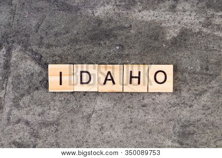 Idaho Word Written On Wood Block, On Gray Concrete Background. Top View.