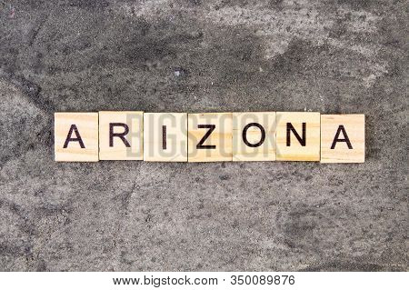 Arizona Word Written On Wood Block, On Gray Concrete Background. Top View.