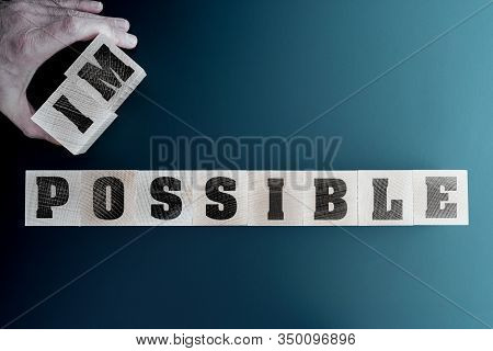 Changing Word Impossible To Impossible On Wooden Blocks, Motivation And Inspiration Concept