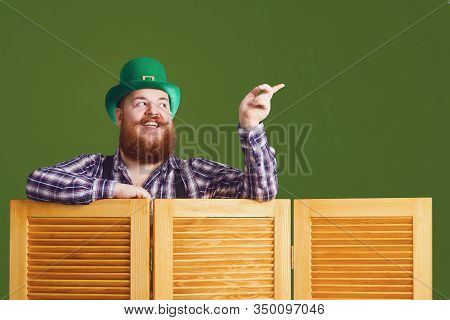 Happy St Patricks Day. Fat Funny Bearded Man Hat Points A Finger At Green Patricks Day Background