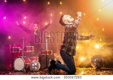 Kids Pretending To Be A Rock Band Play And Sing At Studio Or Stage. Boy Singing And Girl Paying On D