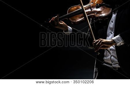 The Violinist In A Tailcoat Plays The Violin On A Dark Background.
