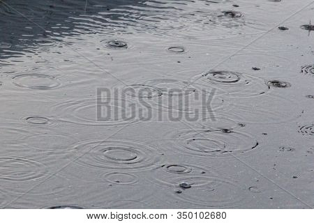 Rain, Raindrops On The Pavement In A Spray Of Water And The Reflection Of Light In Water