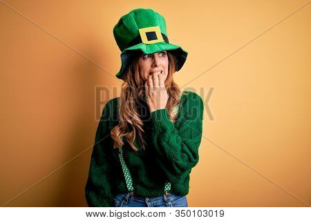 Beautiful brunette woman wearing green hat with clover celebrating saint patricks day looking stressed and nervous with hands on mouth biting nails. Anxiety problem.