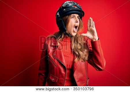 Young beautiful brunette motrocyclist woman wearing moto helmet over red background shouting and screaming loud to side with hand on mouth. Communication concept.