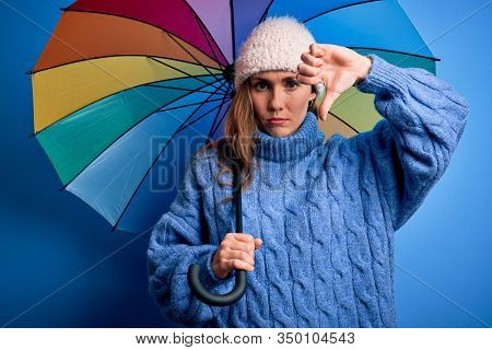 Young beautiful blonde woman holding colorful umbrella over isolated blue background with angry face, negative sign showing dislike with thumbs down, rejection concept