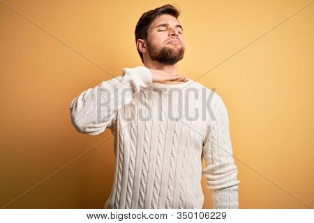 Young blond man with beard and blue eyes wearing white sweater over yellow background cutting throat with hand as knife, threaten aggression with furious violence