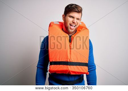 Young blond tourist man with beard and blue eyes wearing lifejacket over white background winking looking at the camera with sexy expression, cheerful and happy face.