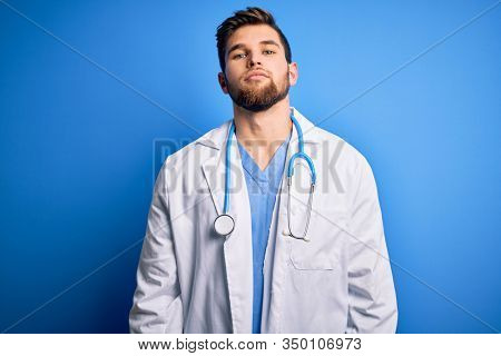 Young blond doctor man with beard and blue eyes wearing white coat and stethoscope Relaxed with serious expression on face. Simple and natural looking at the camera.