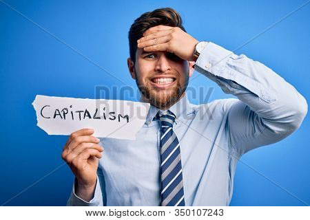 Young blond businessman with beard and blue eyes holding paper with capitalism message stressed with hand on head, shocked with shame and surprise face, angry and frustrated. Fear and upset
