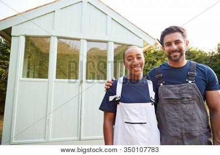 Portrait Of Proud Couple Standing In Front Of Completed Outdoor Summerhouse In Garden