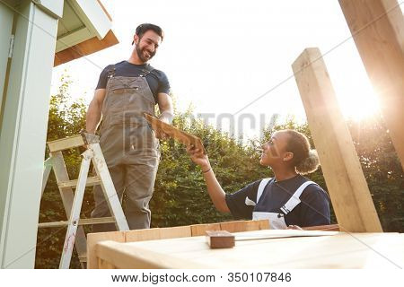 Male Carpenter With Female Apprentice Putting Roof On Outdoor Summerhouse In Garden