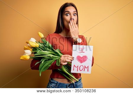 Beautiful woman celebrating mothers day holding love mom message and bouquet of tulips cover mouth with hand shocked with shame for mistake, expression of fear, scared in silence, secret concept