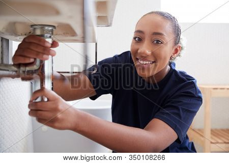 Portrait Of Female Plumber Working To Fix Leaking Sink In Home Bathroom