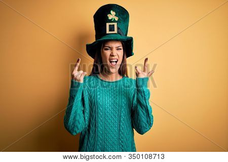Young beautiful brunette woman wearing green hat with clover celebrating saint patricks day shouting with crazy expression doing rock symbol with hands up. Music star. Heavy concept.