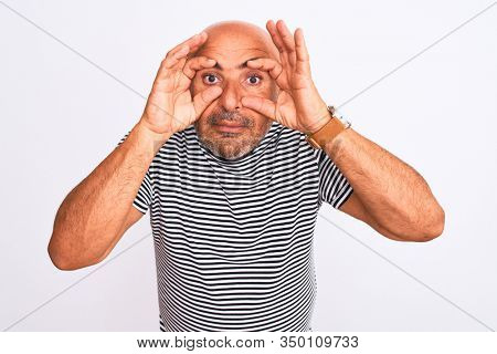 Middle age handsome man wearing striped navy t-shirt over isolated white background Trying to open eyes with fingers, sleepy and tired for morning fatigue