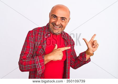 Middle age handsome man wearing casual shirt standing over isolated white background smiling and looking at the camera pointing with two hands and fingers to the side.