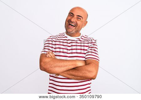 Middle age handsome man wearing striped t-shirt standing over isolated white background happy face smiling with crossed arms looking at the camera. Positive person.