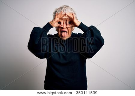 Senior beautiful woman wearing casual black sweater standing over isolated white background doing ok gesture like binoculars sticking tongue out, eyes looking through fingers. Crazy expression.