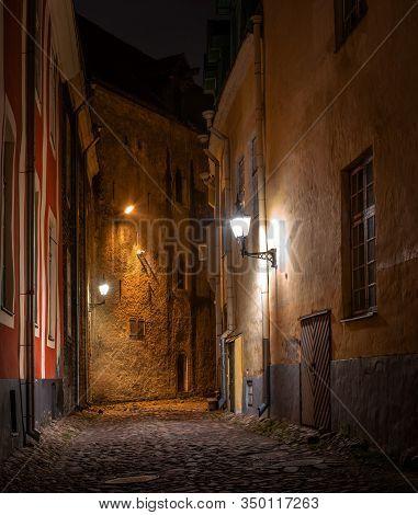 Night Street In The Old Town Of Tallinn, Estonia. Vintage Lanterns Illuminate An Empty Street And Co