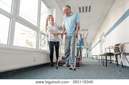 Seniors in rehabilitation learning how to walk with crutches after having had an injury