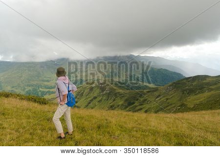 Woman On The Mountain Side Under Low Clouds. A Mountain Valley In The Caucasian Mountains. The Far M