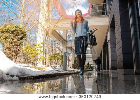 Woman walking through the puddles of the city in pre-spring